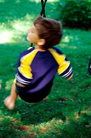 Rear view of a boy playing on a swing