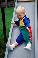 Baby boy coming down a slide in a park