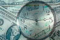 Close_up of a clock superimposed over American dollar bills