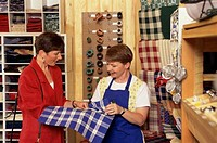 Two mid adult women choosing fabric in a store