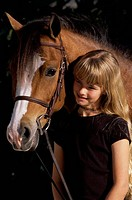 Portrait of a girl holding a Welsh pony