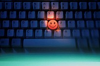 Glowing smiley face on a computer keyboard