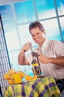 Young man making orange juice