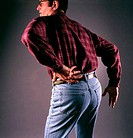 Rear view of a mid adult man bending forward touching his back in pain
