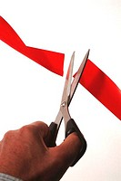 Person's hand using a pair of scissors to cut a red ribbon