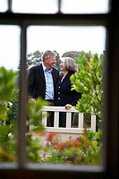 Senior couple standing in a garden and smiling