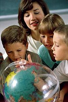Teacher and her children studying the globe