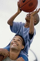 Father carrying his son playing basketball
