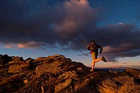 Rear view of a man running on rocks at sunset, Lake Tahoe, California, USA