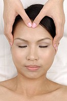 Young woman getting face massage from a massage therapist