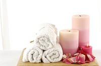 candles burning near rolled towels