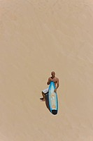 Surfer stands on dune woith surf board