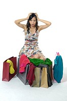 Woman shocked while looking at clothes near shopping bags (thumbnail)