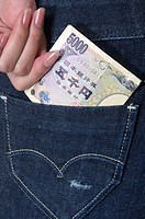 Woman putting Chinese currency in her jeans pocket