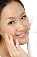 Young beautiful woman with cotton swab cleaning her face (thumbnail)