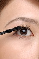 Closeup portrait of an eye of a young pretty woman applying mascara over white background