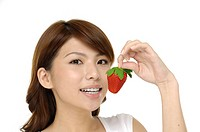 portrait of a beautiful woman holding strawberry