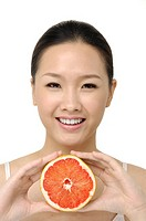 Pretty smiling woman with grapefruit