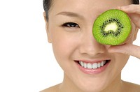 Asian woman holding kiwi fruit in front of face