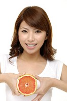smiling asian female face with fresh grapefruit in her hands