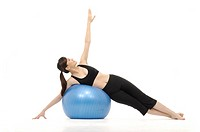Young woman doing yoga with a fitness ball