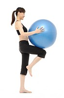 Woman exercising with fitness ball (thumbnail)