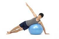 Young man doing yoga with a fitness ball