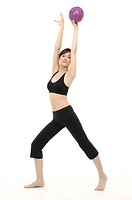 Young woman doing stretching exercise with fitness ball (thumbnail)