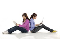 Female university students sitting back to back and using laptops
