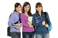 Three female university students holding books and smiling