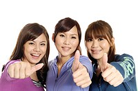 Three female university students showing thumbs up sign