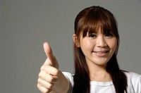 Female university student showing thumbs up sign