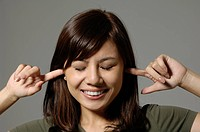 Female university student with fingers in ears