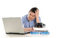 Male university student looking stressed in front of a laptop