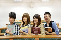 University students holding books and smiling in a classroom