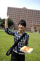 Male university student waving his hand and smiling