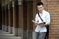 Male university student reading a book