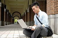 Male university student using a laptop in the corridor
