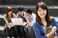 Female university student smiling with her friends using a laptop behind her