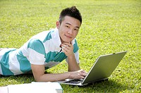Male university student using a laptop in a lawn