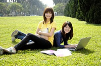Female university students studying in a lawn