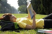 Female university student reading a book in a lawn