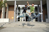 Male university students jumping with holding hands