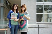 Female university students holding books and standing together
