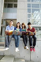 University students holding books and sitting together