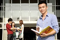 Male university student holding a book with his friends standing behind him