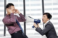 Businesswoman yelling into a megaphone at her colleague (thumbnail)