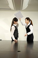 Businesswoman beating her colleague with a file