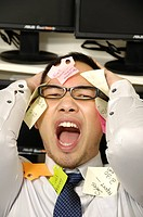 Adhesive notes stuck on a businessman's face