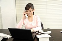 Businesswoman talking on the telephone and using a laptop